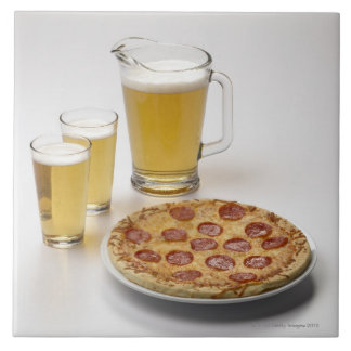Pitcher and two pints of beer beside pepperoni tile