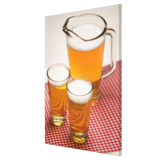 Pitcher of beer and two glasses filled with beer canvas print