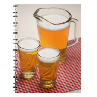 Pitcher of beer and two glasses filled with beer notebooks