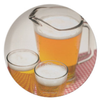 Pitcher of beer and two glasses filled with beer plate