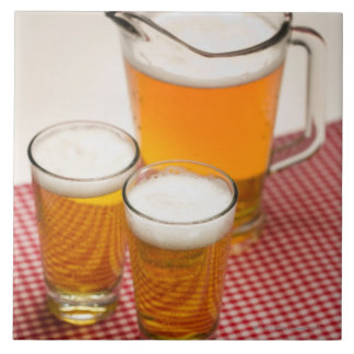 Pitcher of beer and two glasses filled with beer tile