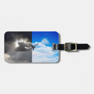 Plane flying out of stormy sky into blue sky luggage tag