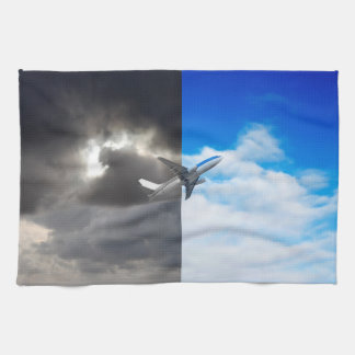 Plane flying out of stormy sky into blue sky tea towel
