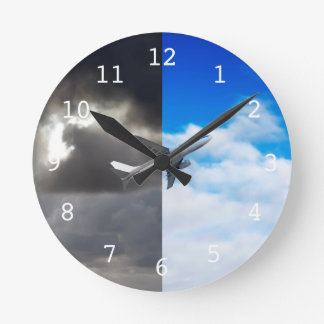 Plane flying out of stormy sky into blue sky wallclock