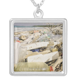 Plastic bottles and ocean dumping on a tropical square pendant necklace