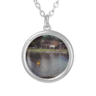 Plastic buoy in front of a lake round pendant necklace