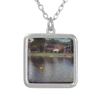 Plastic buoy in front of a lake square pendant necklace