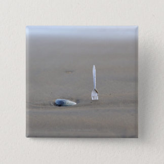 plastic fork sticking in sandy beach beside 15 cm square badge