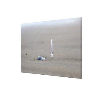 plastic fork sticking in sandy beach beside canvas print