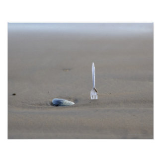 plastic fork sticking in sandy beach beside poster