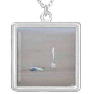plastic fork sticking in sandy beach beside silver plated necklace