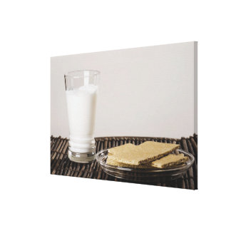 Plate of snacks with a glass of milk canvas print