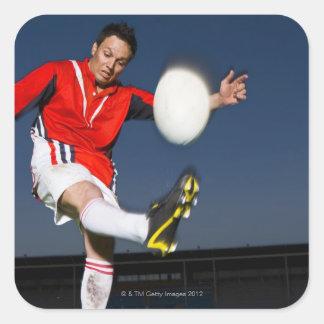 Player kicking ball square sticker