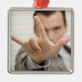 Portrait of a businessman making a hand sign christmas ornament