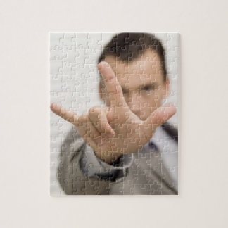 Portrait of a businessman making a hand sign jigsaw puzzle