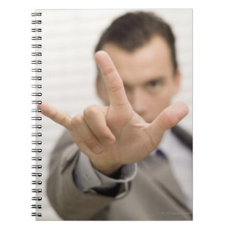 Portrait of a businessman making a hand sign spiral notebook