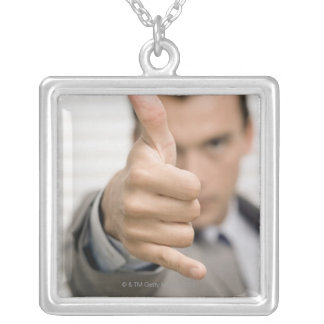 Portrait of a businessman making a thumbs up silver plated necklace