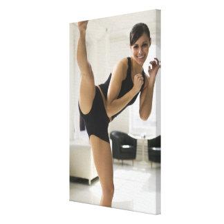 Portrait of a woman kicking canvas print
