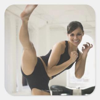 Portrait of a woman kicking square sticker