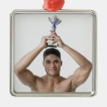 Portrait of a young man holding a trophy christmas ornaments