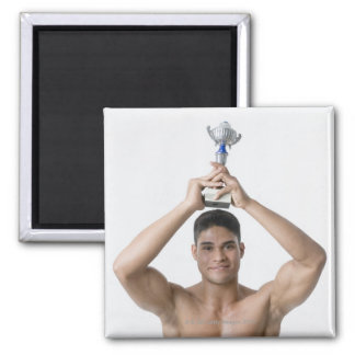 Portrait of a young man holding a trophy square magnet