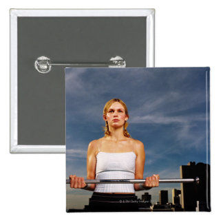 Portrait of a young woman carrying a barbell 15 cm square badge