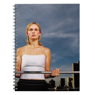 Portrait of a young woman carrying a barbell notebook