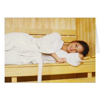 Portrait of a young woman lying in a sauna greeting card
