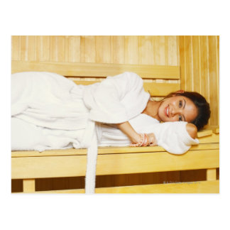 Portrait of a young woman lying in a sauna postcard