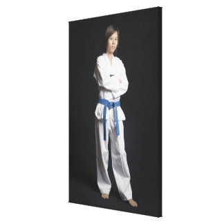 Portrait of a young woman standing with her arms canvas print
