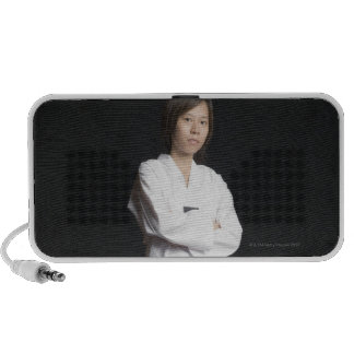 Portrait of a young woman standing with her arms mp3 speakers