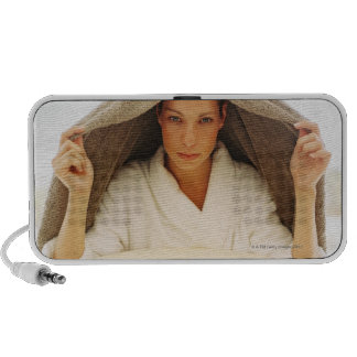 portrait of a young woman with a towel over her laptop speaker