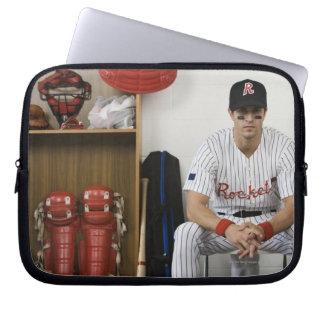 Portrait of baseball player sitting in locker laptop sleeve