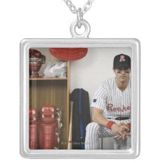 Portrait of baseball player sitting in locker silver plated necklace
