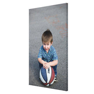 Portrait of boy with basketball outdoors canvas print