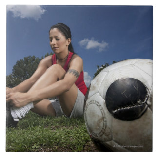 portrait of female football player tying her large square tile