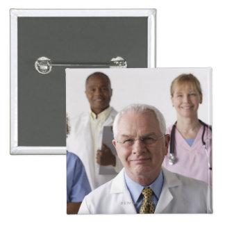 Portrait of four medical professionals, studio buttons