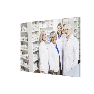 Portrait of four smiling pharmacists canvas print