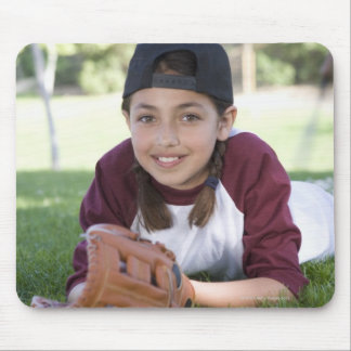 Portrait of girl lying on ground with baseball mouse mat