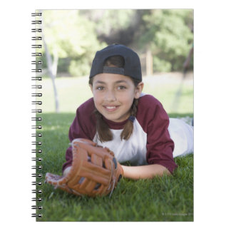 Portrait of girl lying on ground with baseball notebooks