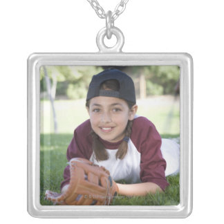 Portrait of girl lying on ground with baseball silver plated necklace