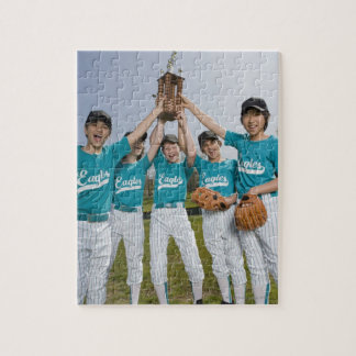 Portrait of little league players with trophy puzzle