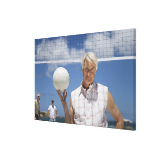 Portrait of mature man holding volley ball on canvas print