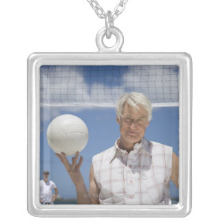 Portrait of mature man holding volley ball on silver plated necklace