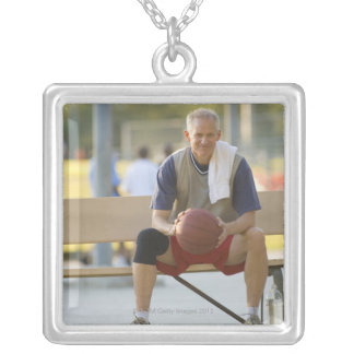 Portrait of mature man with basketball sitting silver plated necklace