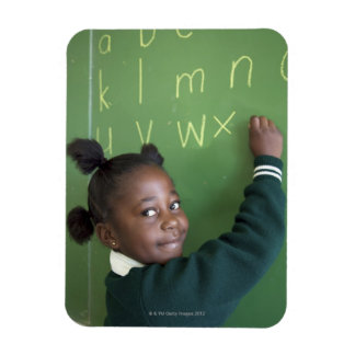 Portrait of smiling schoolgirl writing on the magnet