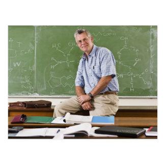 Portrait of teacher sitting on desk in front of postcard