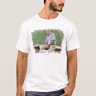 Portrait of teacher sitting on desk in front of T-Shirt