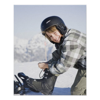 Portrait of young boy kneeling to tie ski boot, poster