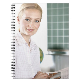 portrait of young female teacher in classroom notebooks